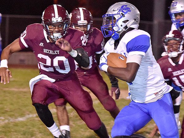 (Brad Davis/The Register-Herald) Woodrow Wilson defender Micah Hancock bears gives chase as Capital's Deishawn Harper turns a corner and picks up big yards Friday night at Van Meter Stadium.