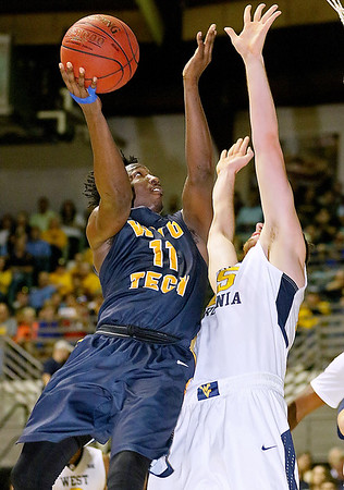 (Brad Davis/The Register-Herald) WVU Tech's Kievonn Banks drives to the basket as WVU's Maciej Bender defends during the Mountaineers' exhibition game with the Golden Bears Saturday night at the Beckley-Raleigh County Convention Center.
