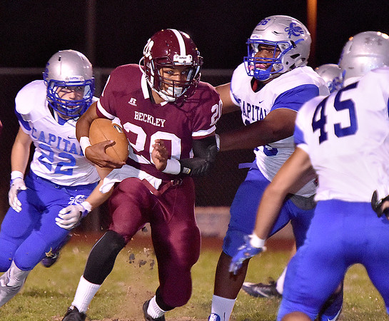 (Brad Davis/The Register-Herald) Woodrow Wilson's Micah Hancock carries the ball during the Flying Eagles' game against Capital Friday night at Van Meter Stadium.