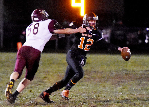 Summers County's quarterback Nathan Grimmett (12) tries to get away from Pocahontas' Mark Jordan (58) during the first quarter of their football game Friday in Hinton (Chris Jackson/The Register-Herald)