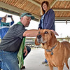 (Brad Davis/The Register-Herald) Jon White, pastor at St. Stephen's Episcopal Church at 200 Virginia Street in Beckley, blesses resident Kayla Smith's (right) dog Clampett under the gazebo at Jim Word Memorial Park Sunday afternoon.