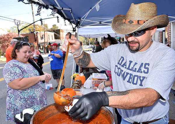 (Brad Davis/The Register-Herald) Matt Stadelman pours a cup of chili for Virginia resident Janie Hayes during the Fayetteville Chili Cook-Off Saturday afternoon on Court Street.