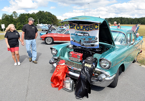 "(Brad Davis/The Register-Herald) Beckley residents Steve and Barbie Wilburn check out all the sweet rides as they pass by Ben ""Superman"" Keeney's 1957 Chevrolet Bel Air (right) during the Friends of Coal Cruise-in Car Show Saturday afternoon at the Raleigh County Memorial Airport."