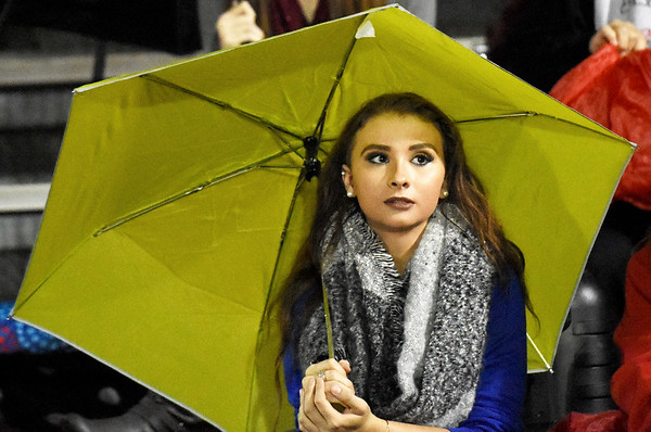 Liberty High School Junior Reanna Richardson, from Lester, looks on under an umbrella during a rainy first quarter of their football game against Midland Trail Friday in Glen Daniel. (Chris Jackson-Register-Herald)