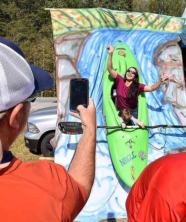 (Brad Davis/The Register-Herald) Beckley resident Leigh Deal poses gloriously as 6-year-old Rowan Meadows looks inside the prop while Ashley Thomas, lower left, shoots during bridge day saturday.