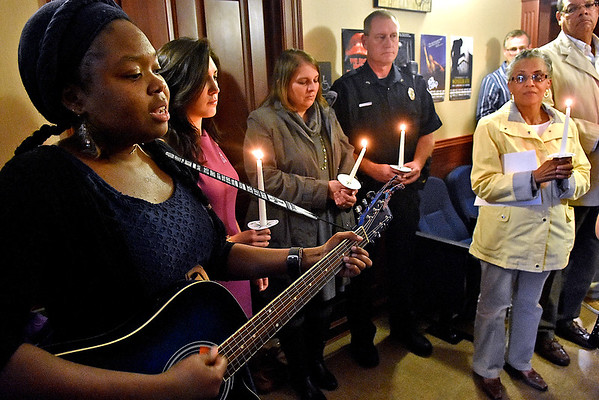 (Brad Davis/The Register-Herald) Attendees take a moment to remember victims of domestic violence as guitarist Jori Williams, left, plays during the Women's Resource Center's 26th annual Candlelight Vigil and memorial service Saturday afternoon at The Raleigh Playhouse & Theatre.