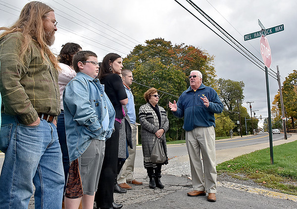 """(Brad Davis/The Register-Herald) Son Chris Hancock, left, grandson Paul Evans (2nd from left, front row), daughter Alisa Evans and several other friends and relatives look on as mayor, friend and highschool classmate Rob Rappold says a few words during a brief ceremony honoring the late Mel Hancock Saturday afternoon. In Hancock's honor, the city has named the former """"A"""" Street on the campus of WVU Tech after him."""