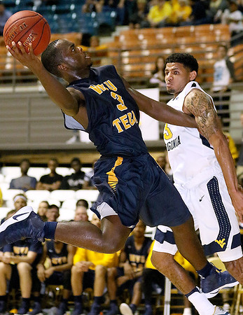 (Brad Davis/The Register-Herald) WVU Tech's Junior Arrey drives to the basket as WVU's James Bolden defends during the Mountaineers' exhibition game with the Golden Bears Saturday night at the Beckley-Raleigh County Convention Center.