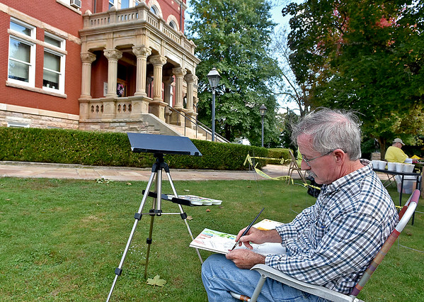 (Brad Davis/The Register-Herald) Pennsylvania artist Jeff Mathison paints a picture of the courthouse in front of him during the New River Plein Air Art Festival going on around Fayetteville's Bridge Day Chili Cook-off Saturday.