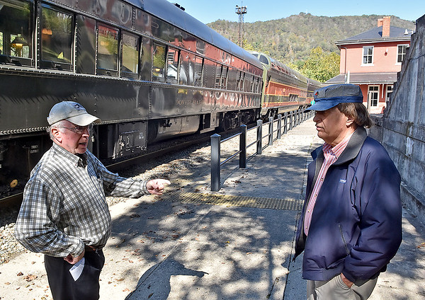 (Brad Davis/The Register-Herald) Railroad buffs Bob Prior, left, and Eddie Sinclair talk trains as they check out all the historic passenger cars of the New River Train during Railroad Days in Hinton Sunday afternoon.