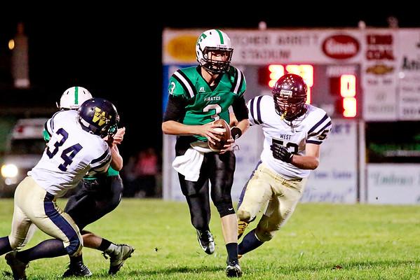Fayetteville quarterback Will Fenton (3) eludes Greenbrier West's Lucas Kessler (53) during their football game Friday in Fayetteville. (Chris Jackson/The Register-Herald)