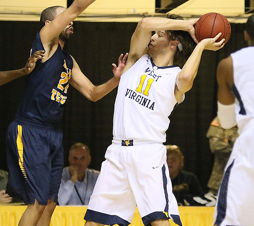 (Brad Davis/The Register-Herald) WVU's Nathan Adrian looks for an open teammate during the Mountaineers' exhibition game with the Golden Bears Saturday night at the Beckley-Raleigh County Convention Center.