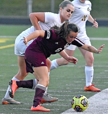 (Brad Davis/The Register-Herald) Woodrow Wilson's Rachel Quattrone tries to shield the ball as Greenbrier East's Adrienne Dye tries to take it Thursday night in Fairlea.