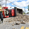 (Brad Davis/The Register-Herald) Beaver volunteer firefighters work the scene of an overturned dump truck and its spilled contents that shut down Ritter Drive for a period of time during the afternoon hours Wednesday afternoon in Beaver.