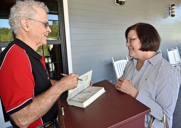 (Brad Davis/The Register-Herald) Rocket boy Homer Hickam signs a book for fan and admirer Carolyn Hamilton during the Rocket Boys Festival Saturday.