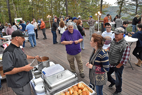 (Brad Davis/The Register-Herald) Foodies meander on the deck of Smokey's on the Gorge as they sample offerings from several area vendors during Taste of Bridge Day Friday evening in Lansing.