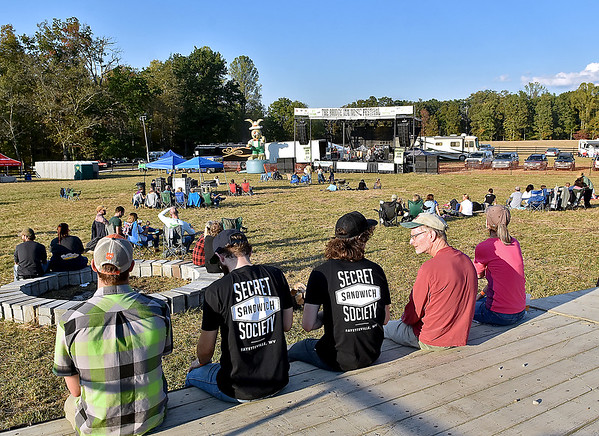 (Brad Davis/The Register-Herald) Fans who arrived early sit scattered around the field area around the stage as they take in a performance from Travers Brothership during the opening moments of Bridge Jam Saturday in Fayetteville.