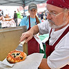 (Brad Davis/The Register-Herald) The Bakery on Court Street's Sandy Carter, right, pulls a fresh mini pizza as his neice and helper Hallee Richmond waits to hand it off to a customer during Taste of Our Town Saturday afternoon in Lewisburg.