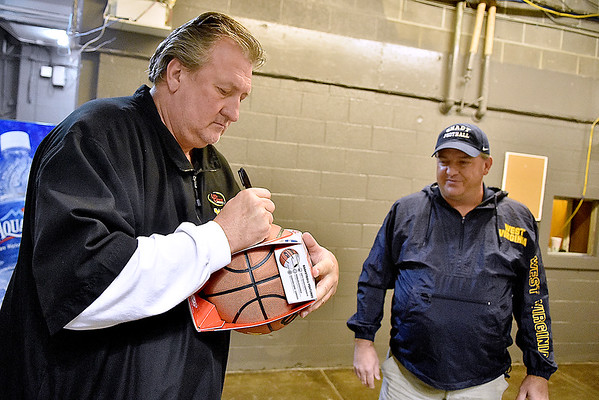 (Brad Davis/The Register-Herald) WVU head coach Bob Huggins signs autographs prior to the Mountaineers' practice Friday night at Beckley-Raleigh County Convention Center.