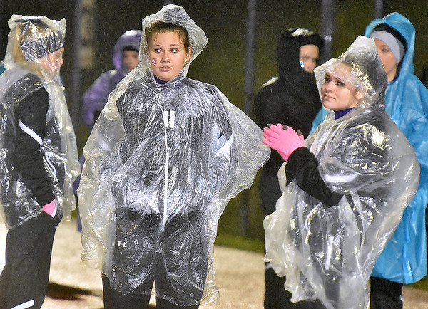 (Brad Davis/The Register-Herald) James Monroe cheerleaders make the best of a rainy situation during the Mavericks' road game at Liberty Friday night in Glen Daniel.