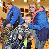 (Brad Davis/The Register-Herald) Five-yaer-old Charlie Fannin tries on a brand new coat with the help of his mother Tiffney, right, while four-year-old Wade Terry (turned at far left) and his mother Renee pick out a coat during Run For The Wall coat and winter clothing giveaway at Rainelle Elementary School Saturday afternoon.