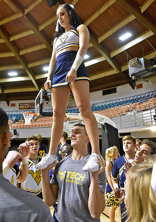 (Brad Davis/The Register-Herald) WVU Tech cheerleader Sean Craze, below, gets a few tips on his lifting technique from his division one counterparts from Morgantown as he holds up WVU cheerleader Mandy Shaffer following a pep rally put on by both the Mountaineers and the WVU Tech Golden Bears cheerleading teams Friday night at Beckley-Raleigh County Convention Center.