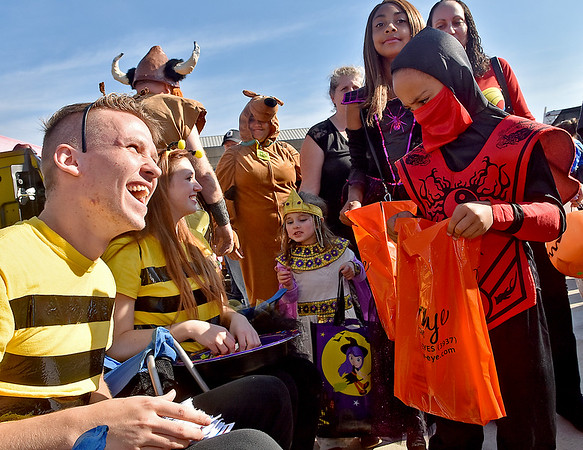 (Brad Davis/The Register-Herald) A sneaky ninja at right, a.k.a. six-year-old Azairias Kimble, moves in to get some some candy from bumblebee impersonators Jacob Blevins and his girlfriend Alex Perkins as they man the Concord University booth during Tailgate Halloween Saturday morning atop Beckley's Intermodal Gateway.