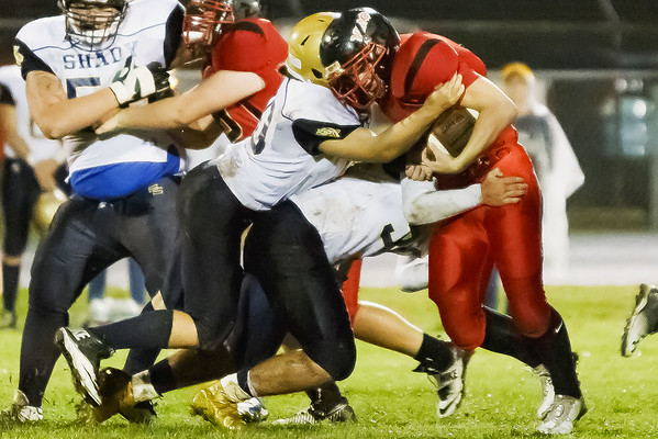 Christian Lively of the Oak Hill Red Devils pushes forward against a pair of Shady Spring Tigers. Chad Foreman for the Register-Herald
