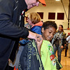 (Brad Davis/The Register-Herald) Rainelle Elementary kindergartener Matthew Bagwell tries on a new coat with the help of veteran and rider Roger Keller, a Campbells Creek resident, during a Run For The Wall coat and winter clothing giveaway Saturday afternoon.