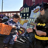 (Brad Davis/The Register-Herald) Five-year-old Zachry Hershberger helps dish out candy with his mom Dina at the Family Worship Center booth during Tailgate Halloween Saturday morning atop Beckley's Intermodal Gateway.