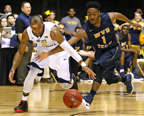 (Brad Davis/The Register-Herald) WVU Tech's Ra'Shaud Kincaid and WVU's Jevon Carter scramble for a loose ball at midcourt during the Mountaineers' exhibition game with the Golden Bears Saturday night at the Beckley-Raleigh County Convention Center.
