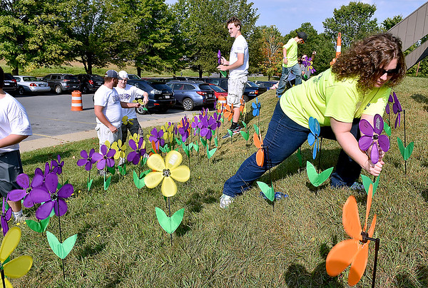 (Brad Davis/The Register-Herald) Volunteers assemble a garden of flowers symbolizing attendees' involvement in the battle against Alzheimer's disease while the teams walk during the annual Walk to End Alzheimer's event Saturday morning at the Beckley-Raleigh County Convention Center. Participants had four different colors of flower to choose from based on their personal experience with the disease. Yellow represents caregivers and supporters of loved ones who have it. Blue represents those currently diagnosed with it, orange stands for supporters of the cause to eliminate the disease and purple represents those who have lost loved ones to Alzheimer's.