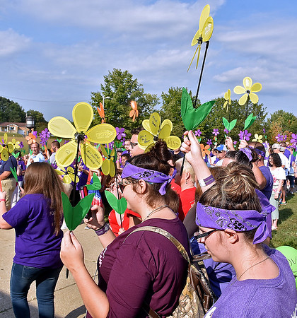 (Brad Davis/The Register-Herald) Attendees hold up their flowers symbolizing their involvement in the battle against Alzheimer's disease during the annual Walk to End Alzheimer's event Saturday morning at the Beckley-Raleigh County Convention Center. Participants had four different colors of flower to choose from based on their personal experience with the disease. Yellow represents caregivers and supporters of loved ones who have it. Blue represents those currently diagnosed with it, orange stands for supporters of the cause to eliminate the disease and purple represents those who have lost loved ones to Alzheimer's.
