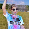 (Brad Davis/The Register-Herald) Kayla Patrick can't contain her enthusiasm for color packets during United Way of Southern West Virginia's Color Me United 5K Walk/Run Sunday afternoon at the Raleigh County Memorial Airport.