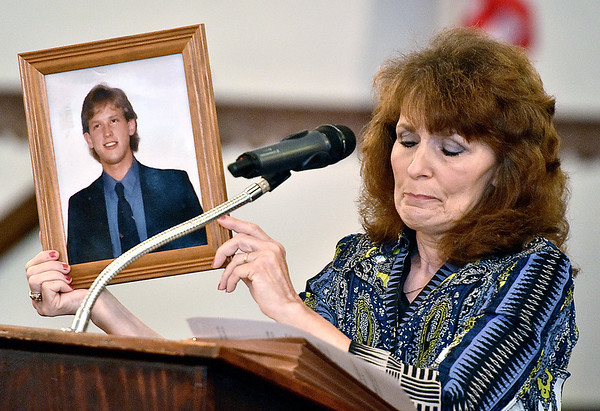 (Brad Davis/The Register-Herald) Crab Orchard resident Donna Rowe tries to keep back tears as she holds up a photo of her late son Travis Summers during a community meeting and discussion on gun violence hosted by Moms Demand Action for Gun Sense in America Saturday afternoon at Heart of God Ministries. Travis went missing May 7, 2014 and was found dead on February 13 of last year.