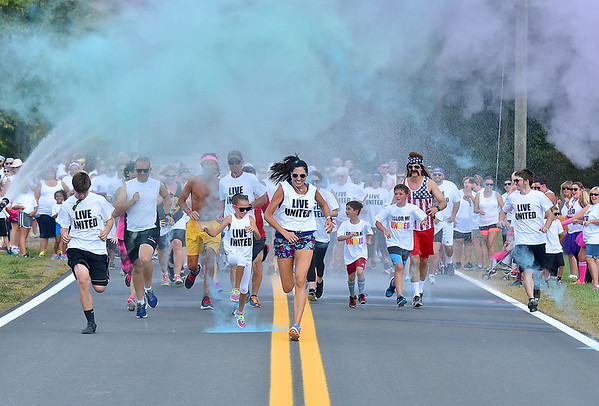 (Brad Davis/The Register-Herald) Participants of this year's United Way of Southern West Virginia's Color Me United 5K Walk/Run take off from the starting line under a cloud of colored powder at the beginning of the event Sunday afternoon at the Raleigh County Memorial Airport.