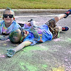 (Brad Davis/The Register-Herald) Young participants Braden Wolfe, right, and Hunter Bowman, both four, didn't think they had enough coloring on their shirts, so they decided to soak up some more by rolling in it during the United Way of Sourthern West Virginia's Color Me United 5K Walk/Run Sunday afternoon at the Raleigh County Memorial Airport.