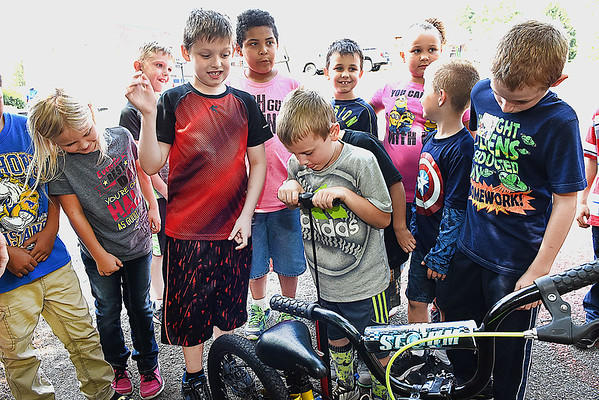 Tray Anderson, center, second grader inTammy Darnell's class at Mt. Hope Elementary School, pumps up a tire during a bike saftely rodeo sponored by Active Southern Vest Virginia.<br /> (Rick Barbero/The Register-Herald)