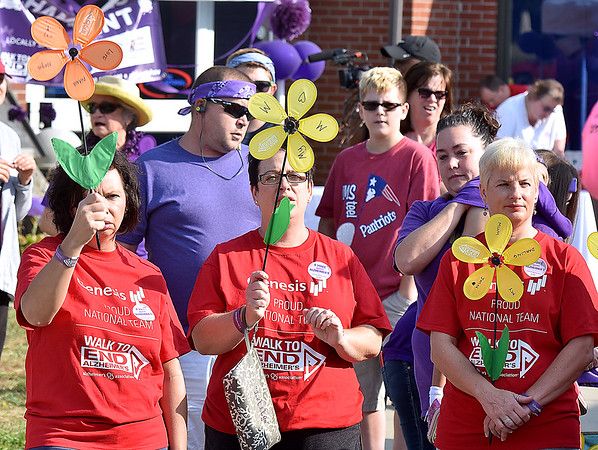 (Brad Davis/The Register-Herald) Attendees hold up their flowers symbolizing their involvement in the battle against Alzheimer's disease during the annual Walk to End Alzheimer's event Saturday morning at the Beckley-Raleigh County Convention Center.