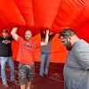 (Brad Davis/The Register-Herald) At right, Danny Acord notices the camera and tries to get clear of it while (From left) Liberty youth football coaches James Acord, Ronnie Harbert and Mike Tolliver hold up the inner middle section of a giant, inflatable Liberty football helmet that was having trouble staying inflated enough before the Raiders entered the field through it against Clay County Friday night in Glen Daniel.