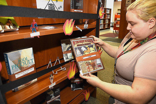 Beth Mills, circulation clerk Raleigh County Public Library in Beckley, looks over books on the library's challenged book display.<br /> (Rick Barbero/The Register-Herald)