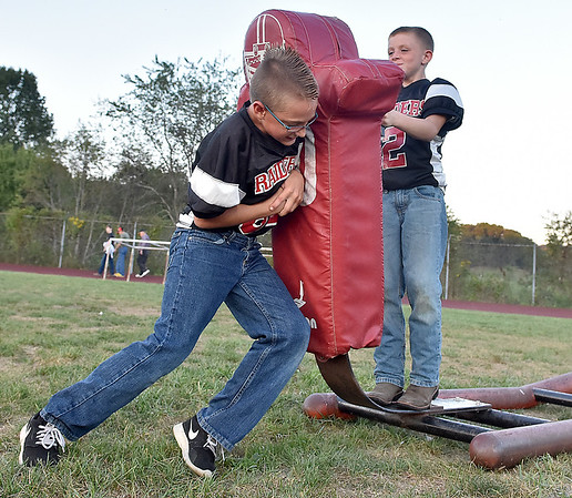(Brad Davis/The Register-Herald) Young football players Riley Marty, left, and Hunter Maynor, both 9, take advantage of the high school team's practice sleds on the field and get few extra reps in prior to greeting the the Raiders onto the field with the rest of their youth football league teammates Friday night in Glen Daniel.