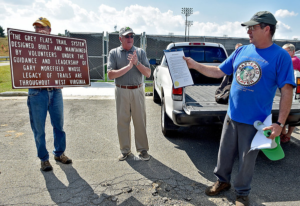 """(Brad Davis/The Register-Herald) A humble Gary Morefield, right, looks over an official proclamation from Beckley mayor Robert Rappold, middle, making September 25th """"Gary Morefield Day"""" as Tom Sopher, left, holds a commemorative sign that will go up near the Grey Flats trail system, which Morefield and several other volunteers helped develop Sunday afternoon at the YMCA Paul CLine Memorial Sports Complex."""