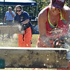 (Brad Davis/The Register-Herald) WVU Forestry student Britani Chambers (upper left) takes on Ohio State student Lauren Kokinda (foreground) in the Women's chainsaw event during the 34th Annual Lumberjackin' Bluegrassin' Jamboree Saturday morning at Twin Falls Resort State Park. A team of WVU students came from Morgantown to take on a group of students and staff from Ohio State University in several lumber jack events, while vendors were on hand and live bluegrass shows commenced later in the day.