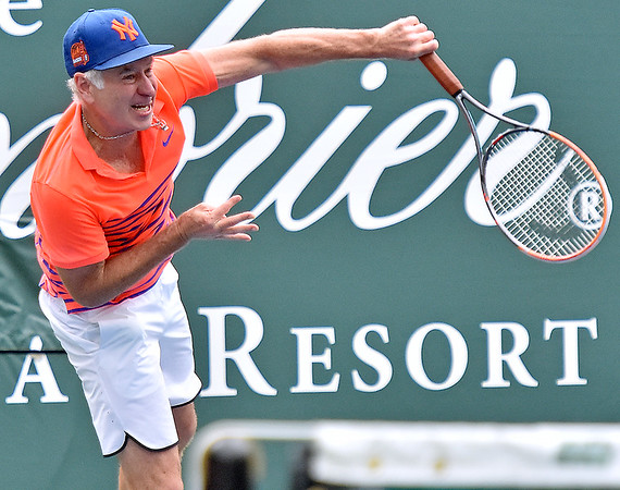 (Brad Davis/The Register-Herald) John McEnroe serves during he and partner Venus Williams' mixed doubles matchup against Pete Sampras and Shelby Rogers during The Greenbrier Champions Tennis Classic Sunday afternoon in White Sulphur Springs.