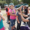 Malorie Polster, community health director Active Southern West Virginia, right, shows childern in Tammy Darnell's second grade class at Mt. Hope Elementary School, how to properly strap helmets on before riding a bike during a bike saftely rodeo. <br /> (Rick Barbero/The Register-Herald)