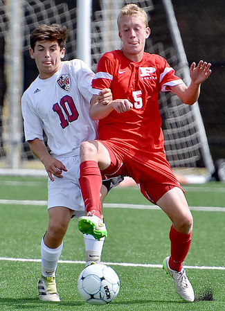 (Brad Davis/The Register-Herald) Woodrow Wilson's Austin Hatfield battles for possession with Parkerburg's Ian Domenick during the Big Reds' win over the Flying Eagles Saturday afternoon at the YMCA Paul Cline Memorial Sports Complex.