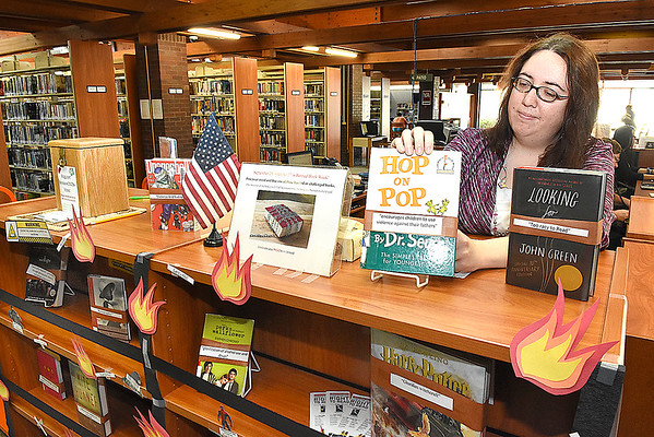 Amy Stover, director Raleigh County Public Library in Beckley, places a Dr. Seuss book on the library's challenged book display.<br /> (Rick Barbero/The Register-Herald)