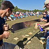 (Brad Davis/The Register-Herald) WVU Forestry students Ryan Fisher and Rene Miller (on the saw) cut as fast as they can while teammate Matt Young applies WD-40 and Matt Stevens (far right) looks in while competing in the Jack & Jill Crosscut event during the 34th Annual Lumberjackin' Bluegrassin' Jamboree Saturday morning at Twin Falls Resort State Park. A team of WVU students came from Morgantown to take on a group of students and staff from Ohio State University in several lumber jack events, while vendors were on hand and live bluegrass shows commenced later in the day.