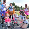 (Brad Davis/The Register-Herald) Three-year-old Raelyn Kiger, right, was perfectly fine getting coated with color, while two-year-old Sophia Mahaffey wasn't so sure about it as a volunteer offered it up Sunday. At upper left is Sophia's mom Ashley, middle is Raelyn's mom Lauren Rizzi and upper right is friend Julia Crittenden.